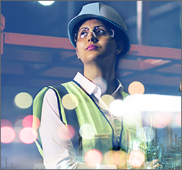 A woman in a hard hat, safety goggles and safety vest surveys a manufacturing plant.